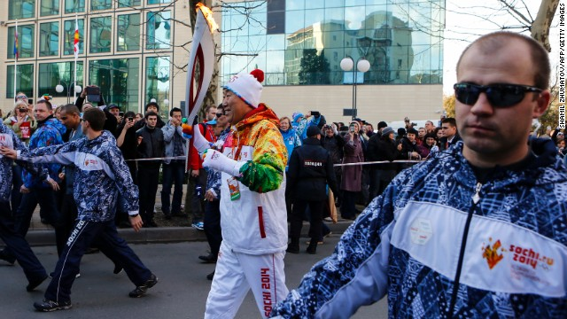 UN Secretary-General Ban Ki-moon is surrounded by security personnel during the Olympic torch relay in Sochi on February 6.
