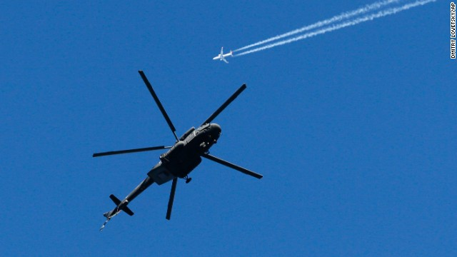 A military helicopter hovers over Krasnaya Polyana as a passenger jet passes by on February 4.