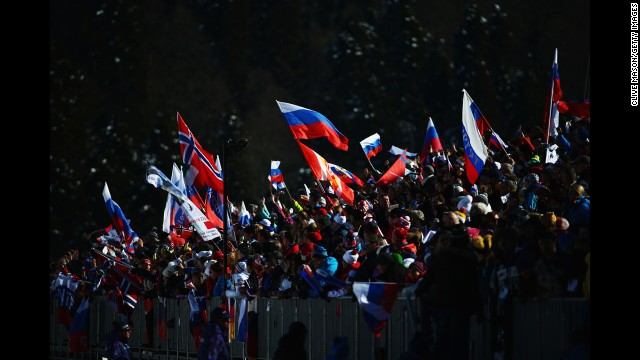 Spectators wave national flags close to the finish line of the women's skiathlon.