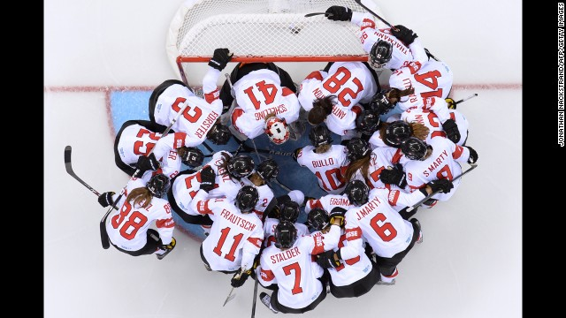 The women's hockey team of Switzerland huddles before the start of its Group A match against Canada.