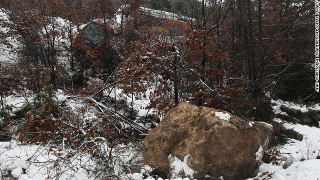 The boulder that caused the derailment sits below the damaged train.