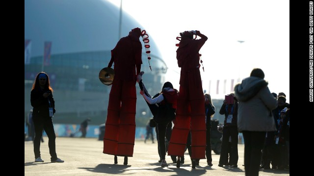 A pair of street performers on stilts help a young woman stretch February 8 at the Olympic village.