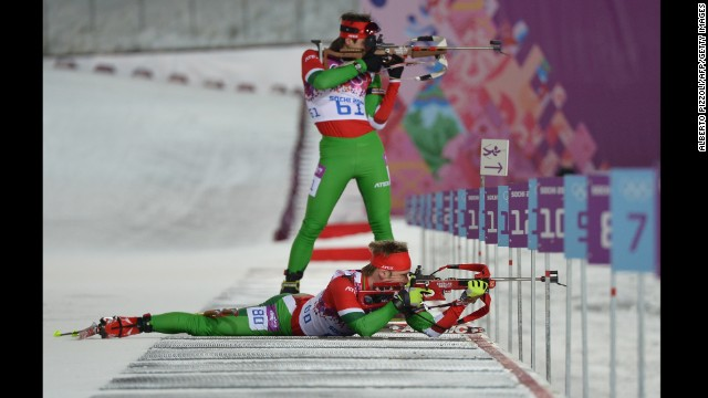 Belarussian biathletes Evgeny Abramenko, standing, and Yuryi Liadov shoot during the men's 10-kilometer sprint on February 8.