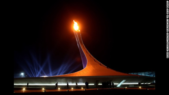 The Olympic flame burns in the cauldron February 8 as people walk in Olympic Park.