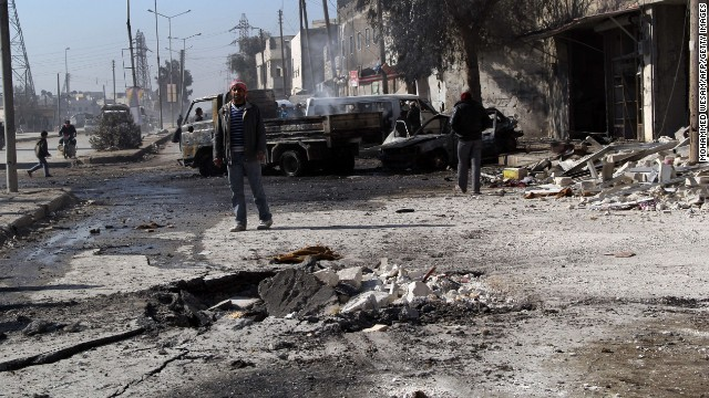 A man stands next to debris in the road following a reported airstrike by Syrian government forces in the northern city of Aleppo on February 8.