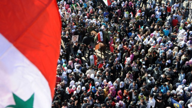 In this handout photo released by the official Syrian Arab News Agency on February 8, civilians wave national flags in Damascus as they take part in a rally in support of President al-Assad.