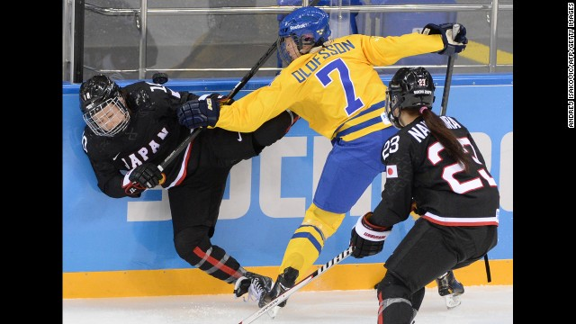 Sweden's Johanna Olofsson, center, vies with Japan's Haruna Yoneyama, left, during their Group B hockey game February 9.
