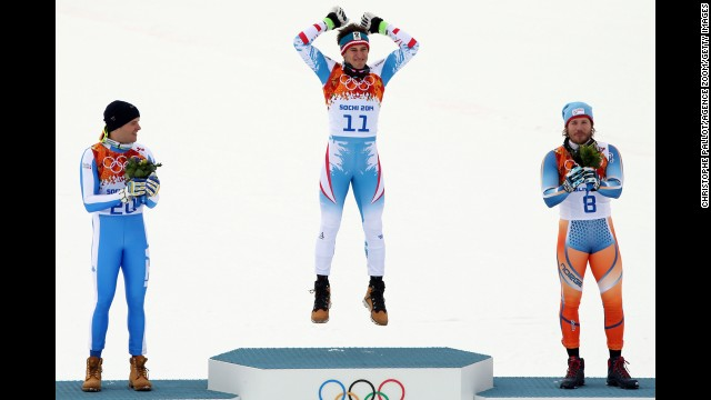 Austria's Matthias Mayer jumps on the medal podium after the downhill event.