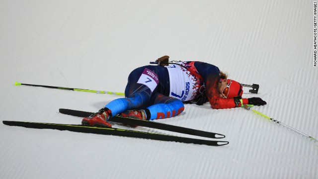 Biathlete Ekaterina Shumilova of Russia collapses on the snow February 9 after crossing the finish line in the women's 7.5-kilometer sprint.