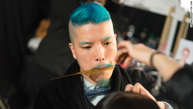 A hairdresser gets a model runway ready for Mathieu Mirano.