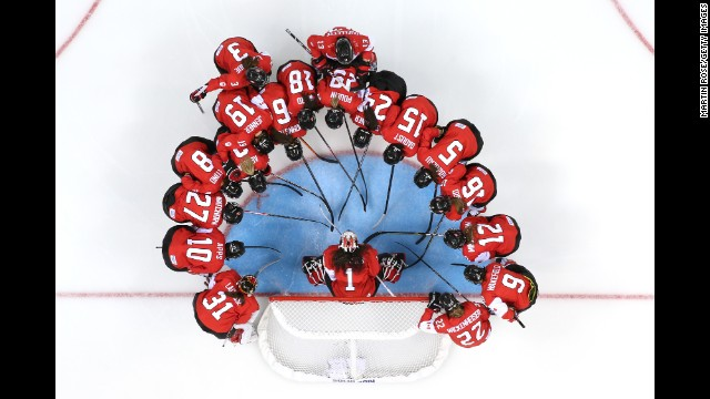 The Canadian women's ice hockey team talks at the net prior to a preliminary round game on February 10.