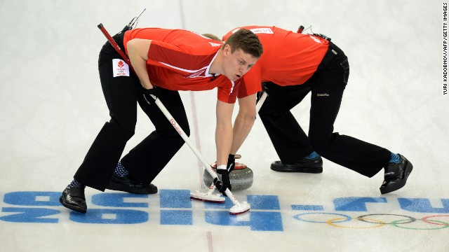 Denmark's Troels Harry, left, and Mikkel Poulsen sweep in front of a curling stone during a match against Russia on February 10.