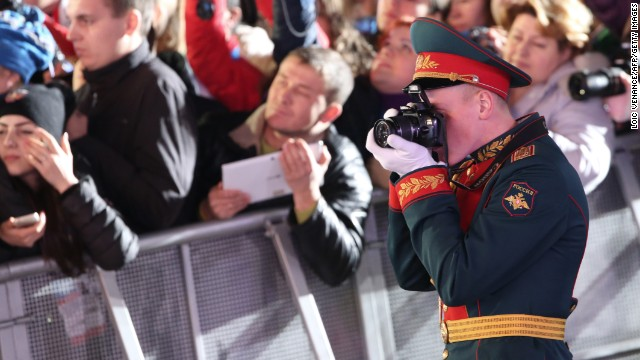 A military officer shoots pictures during the medal ceremony for team figure skating on February 10.