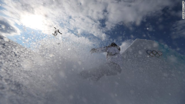 A competitor takes a jump as a team member follows during slopestyle training on February 10.