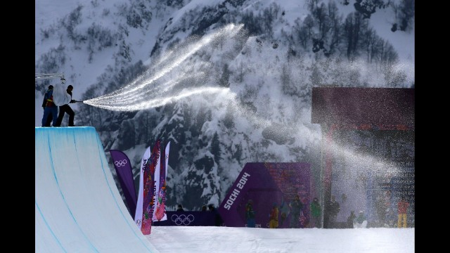 Workers spray down the halfpipe before competition begins in men's snowboarding February 11.