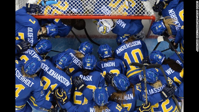 Sweden's players gather at the net before the women's Group B hockey match between Sweden and Germany on February 11.