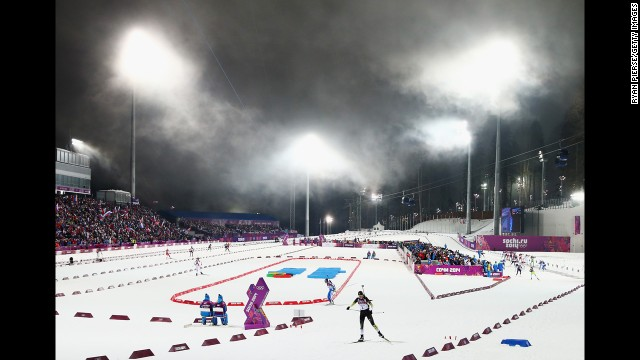 Slovakian biathlete Anastasiya Kuzmina, foreground, skis away from the shooting range during the 10-kilometer pursuit on February 11.