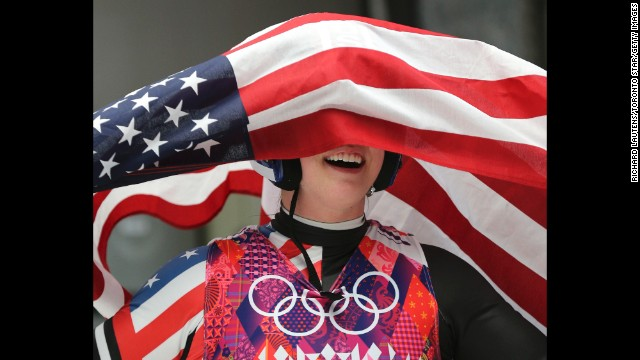 Erin Hamlin is covered by the American flag after she finished third in the women's luge on February 11.
