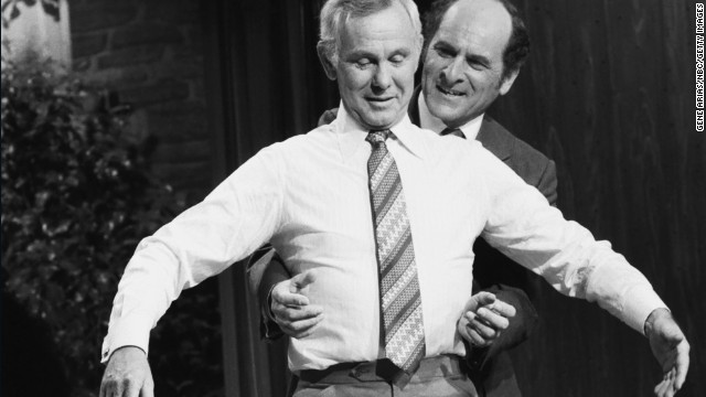 Dr. Henry Heimlich demonstrates the Heimlich maneuver on host Johnny Carson while appearing on