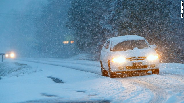 Vehicles slowly make their way over a snow-covered Route 35 in Fort Payne, Alabama, on February 11.