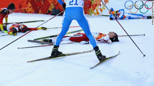Skiers fall to the ground after the cross-country portion of the men's Nordic combined event February 12.
