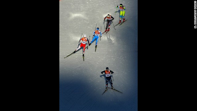 Eetu Vaehaesoeyrinki of Finland leads a group of skiers during the men's Nordic combined on February 12.