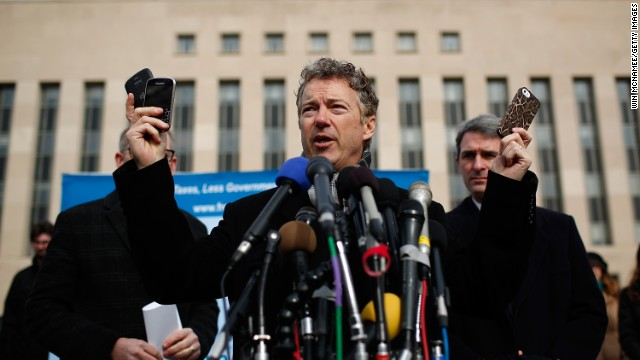 Sen. Rand Paul holds cell phones in front of federal court in Washington to announce a class-action lawsuit against the Obama administration over NSA surveillence.