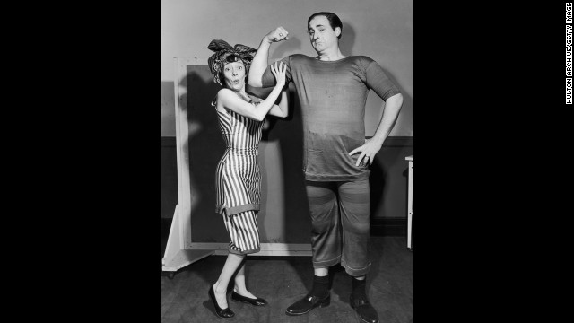 Imogene Coca feels Caesar's biceps as he mockingly flexes circa 1955. They are both dressed in period bathing suits.