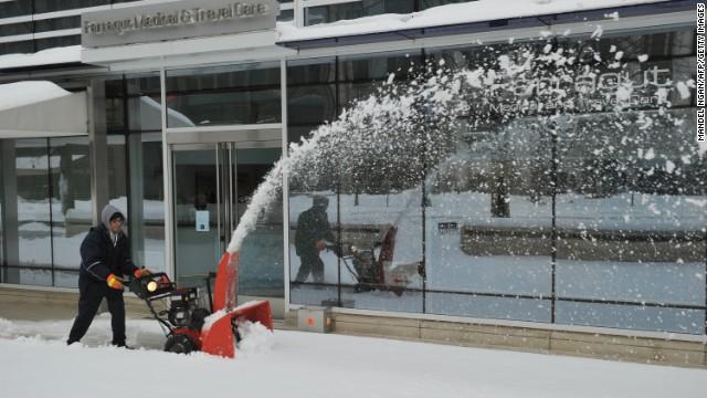 A worker clears a snowy sidewalk in Washington on February 13.