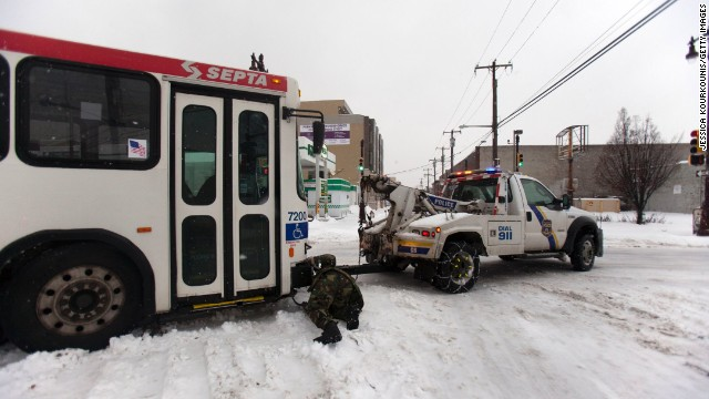 Police work to tow a bus that slid off the road in Philadelphia on February 13.
