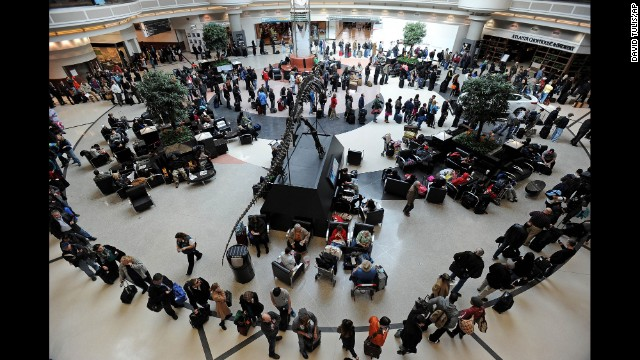 A long line of travelers winds around the atrium of Hartsfield-Jackson Atlanta International Airport on February 13 as people attempt to catch flights previously canceled because of th