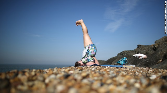 A woman practices yoga on a British beach. Suzanne Steinbaum says
