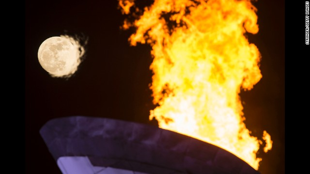 The Olympic flame burns under a full moon on February 13.