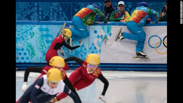 Track wardens attempt to clear the way as Fan Kexin of China crashes in the semifinals of the women's 500-meter short track speedskating competition on February 13.