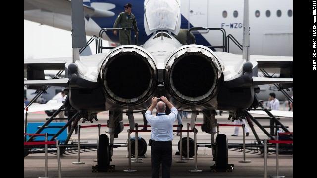 An attendee takes a photograph of the Boeing Co. F-15SG Strike Eagle fighter jet on February 11.
