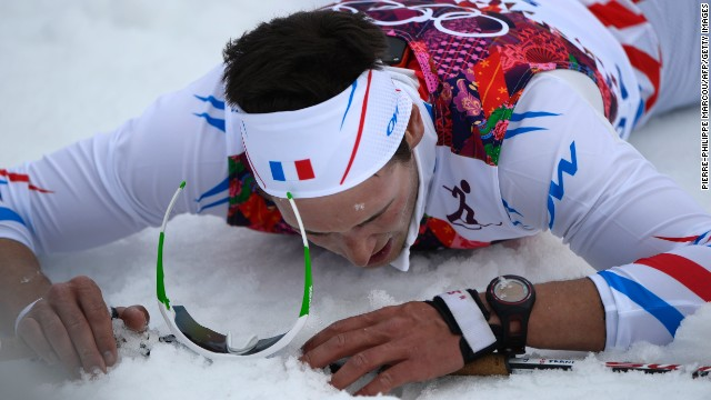 French skier Adrien Backscheider lies on the snow after the men's 15-kilometer classic.