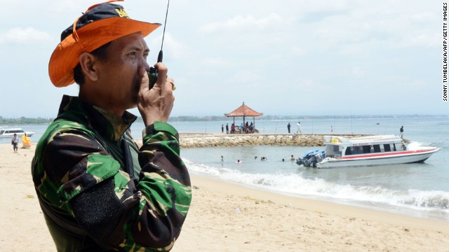 An Indonesian rescue officer monitors a search team at a Bali beach on Sunday.