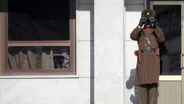 "A North Korean soldier uses binoculars on Thursday, February 6, to look at South Korea from the border village of Panmunjom, which has separated the two Koreas since the Korean War. A new United Nations report describes a brutal North Korean state ""that does not have any parallel in the contemporary world."""
