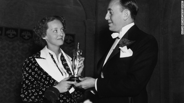 "Bette Davis and film producer Jack L. Warner hold Davis' best actress Oscar at the ceremony held in 1936. Davis won her first Oscar for her role in the film ""Dangerous."""