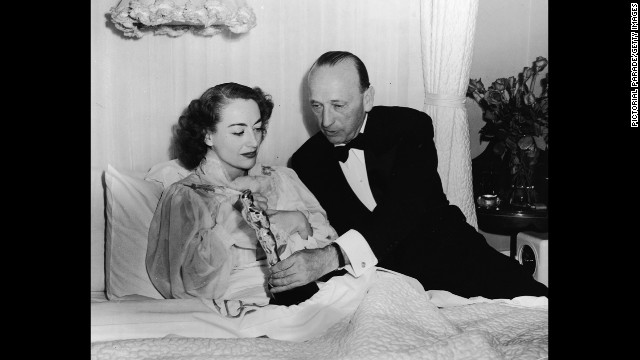 "Joan Crawford receives her Academy Award in bed because of an illness. She was recognized for her performance in the 1945 film ""Mildred Pierce."""