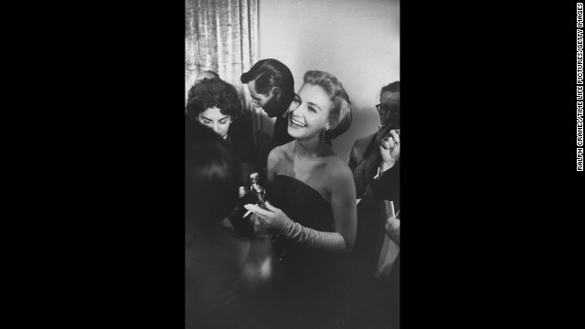 "Joanne Woodward smiles while holding her best actress Oscar (and a cigarette). She received the award for her role in the film ""Three Faces of Eve."""