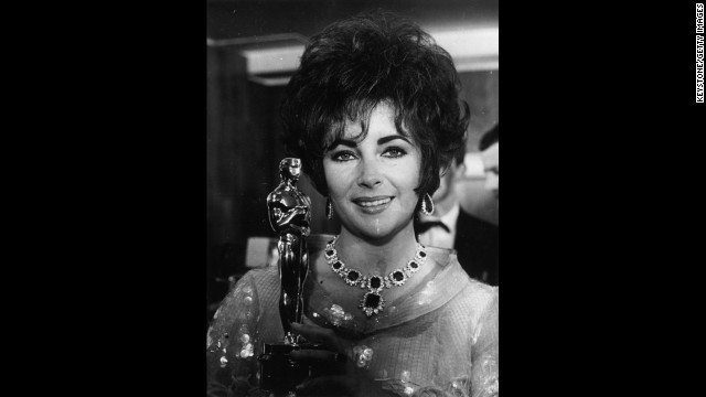 "Elizabeth Taylor holds up her second Oscar, this one for the film ""Who's Afraid of Virginia Woolf."""