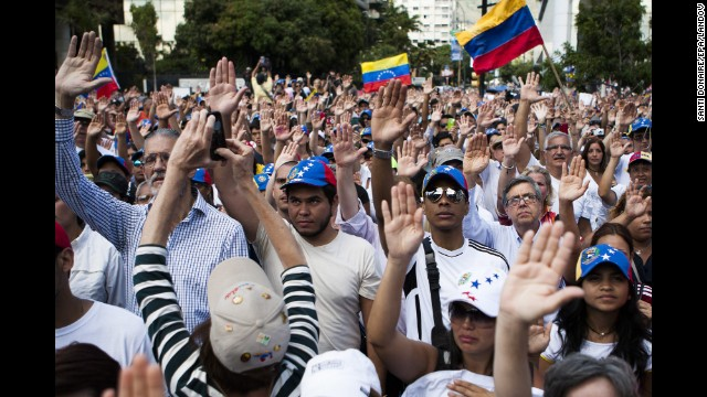 A group of protesters raise their hands during a demonstration in Caracas on Sunday, February 16. The country has an inflation rate of 56.2%, the highest in the world, and many basic goods are missing from store shelves.