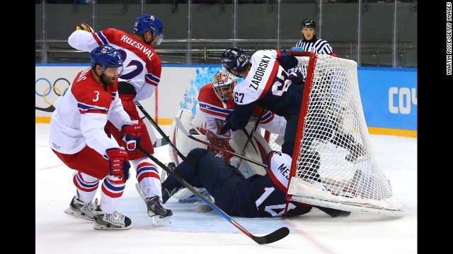 Slovakian hockey players Andrej Meszaros and Tomas Zaborksy crash into Czech goalie Ondrej Pavelec on February 18.