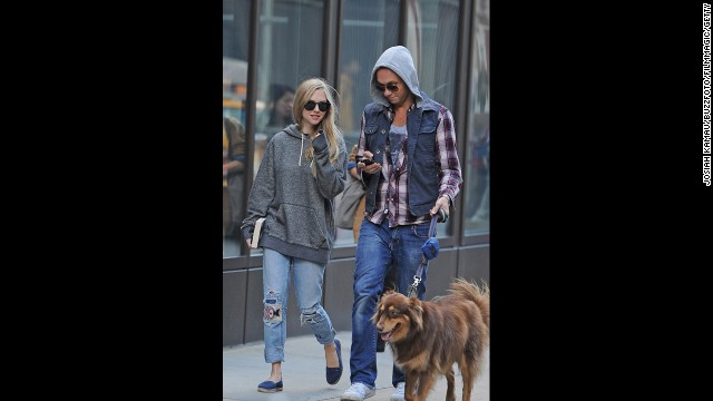 Actress Amanda Seyfried, left, wears shredded jeans and an oversized sweatshirt while walking her dog through Washington Square Park in New York City.