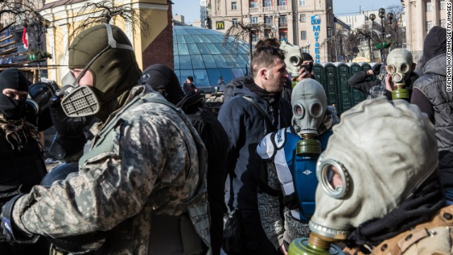Protesters put on gas masks near the perimeter of Independence Square on February 19.