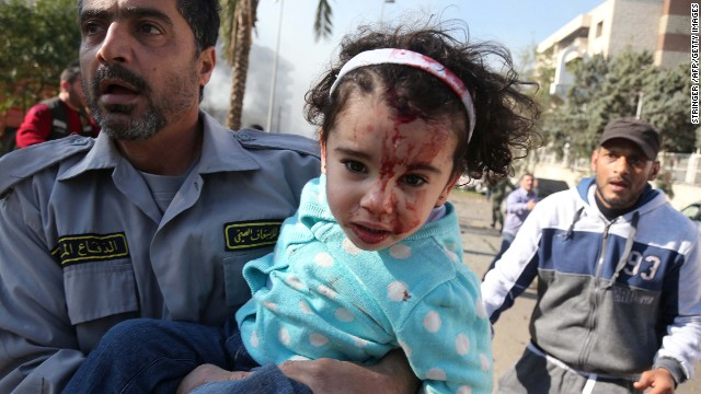 Lebanese emergency personnel evacuate an injured girl from an orphanage in Beirut on February 19, 2014.