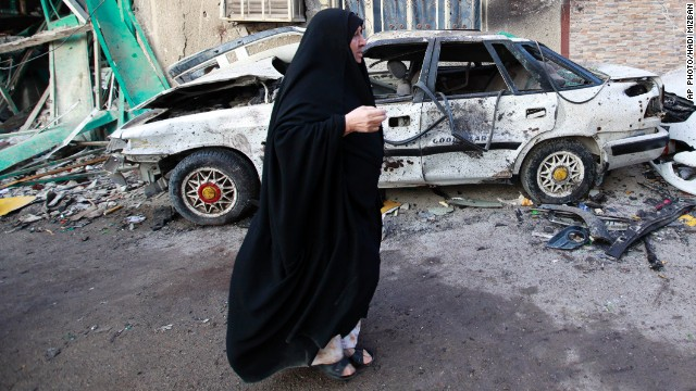 A woman walks past the site of a car bomb attack in Baghdad, Iraq on February 18, 2014.