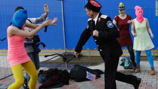 "A man in a Cossack uniform attacks Pussy Riot band member Nadezhda Tolokonnikova and a photographer during a protest performance in Sochi, Russia, on Wednesday, February 19. The band said it was attacked by security officials while trying to perform a new song called ""Putin teaches us to love our motherland"" at the main port in Sochi."