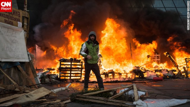 A Ukrainian protester stands in front of the burning Euromaidan protest camp in Kiev on Wednesday February 18. Protesters set up tents in the square in December, says iReporter and American journalist <a href='http://ireport.cnn.com/docs/DOC-1087484'>Chris Collison</a>.